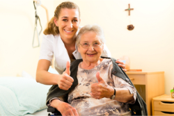 Nurse and senior doing the thumbs-up sign