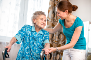 caregiver assisting her patient in walking